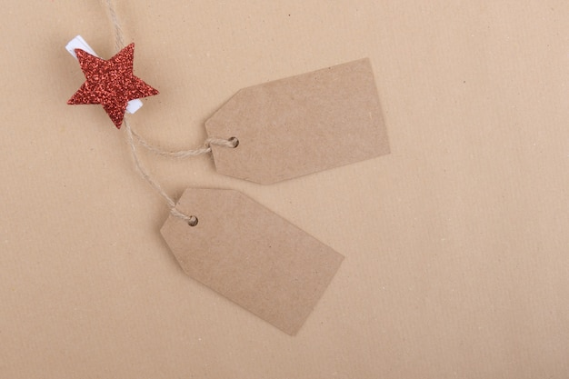 Two tags of recycled kraft paper hanging from a rope decorated with a clothespin with a red christmas star Premium Photo
