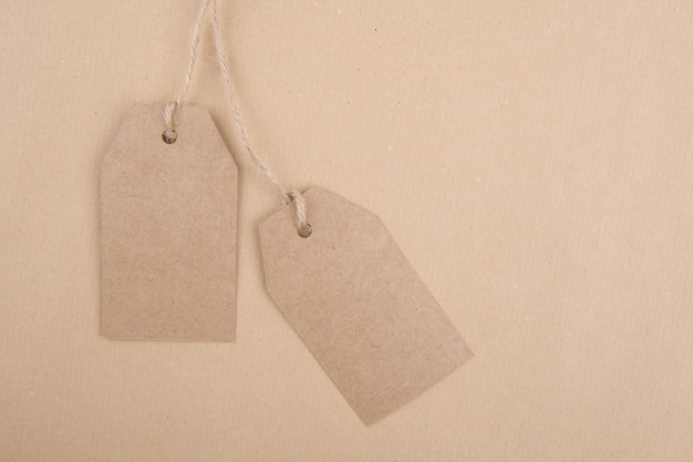 Two tags of recycled kraft paper  hanging from a rope on kraft paper. flat lay Premium Photo