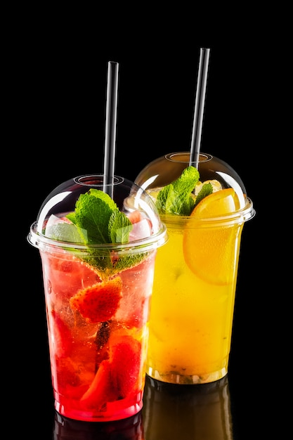Two take away glasses with strawberry and orange lemonade isolated on black Premium Photo