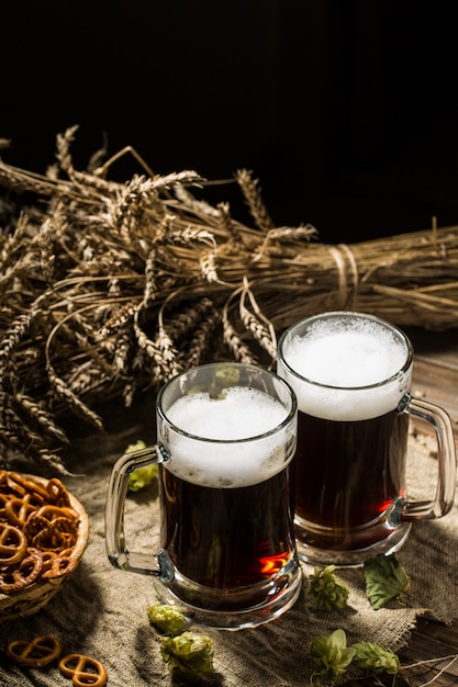 Two tankard beer with wheat and hops, basket of pretzels Premium Photo