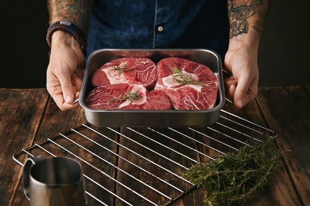Due mani tatuate offrono un pezzo di ottima bistecca di carne in una padella di acciaio argentato con spezie con osso sulla fotocamera Foto Gratuite