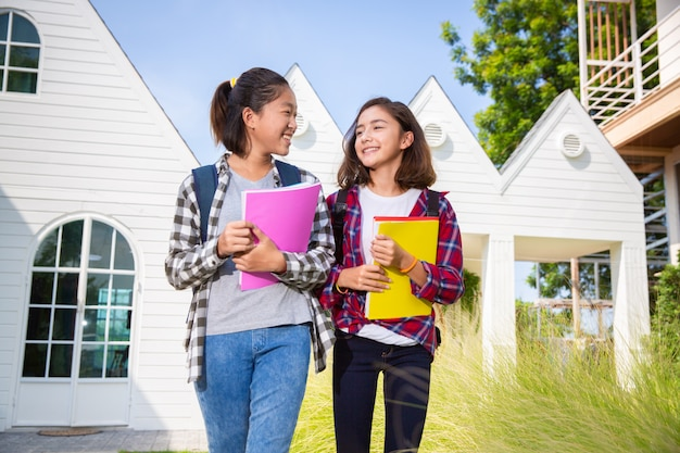 Two teenage asia and european student friends girls happy going to college or school,diverse ethnicities Premium Photo