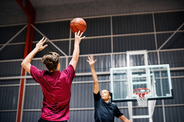 Two teenage boys playing basketball together on the court Premium Photo