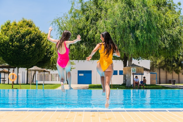 Two teenage girls jumping in a swimming pool. two girls jumping into a swimming pool Premium Photo