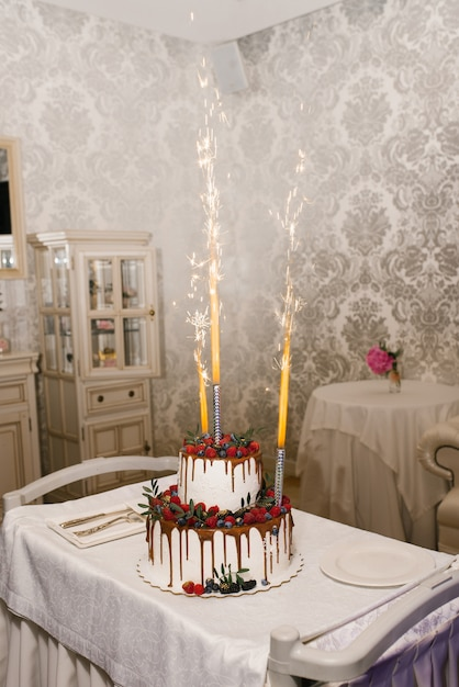 A two tier wedding white cake with years of raspberries and blackberries and a fountain of fireworks in the cake Premium Photo