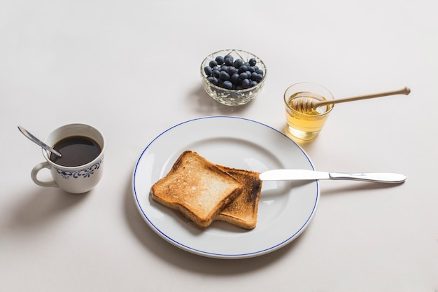 Two toast bread with honey; tea and blueberries on white background Free Photo