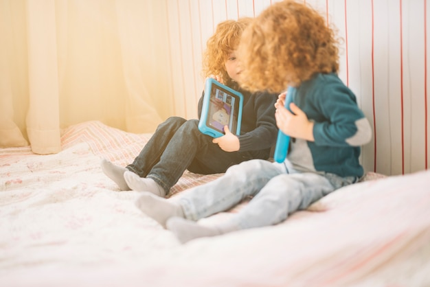 Two toddlers sitting on bed playing with digital tablet Free Photo