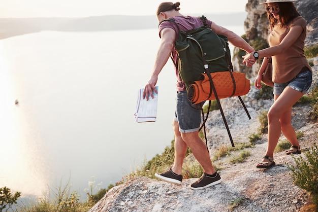 バックパックを持った2人の観光客が山の頂上に登り、日の出を楽しむ 無料写真