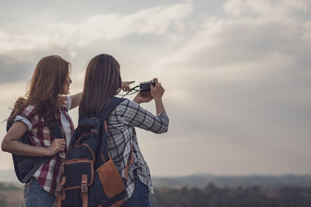 Two tourist woman taking a photo with camera in nature Premium Photo