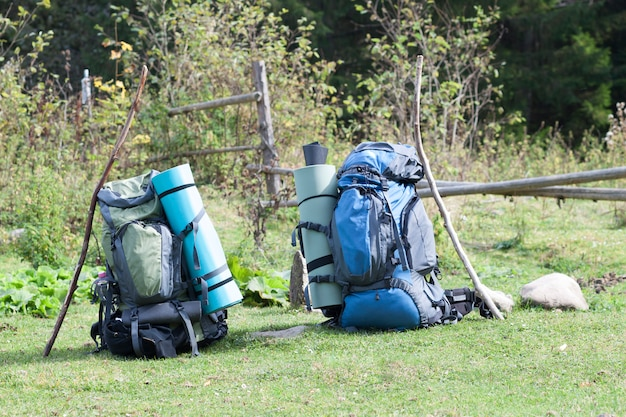 Two touristic hikers backpacks standing in a mountain valley on sunny day Premium Photo