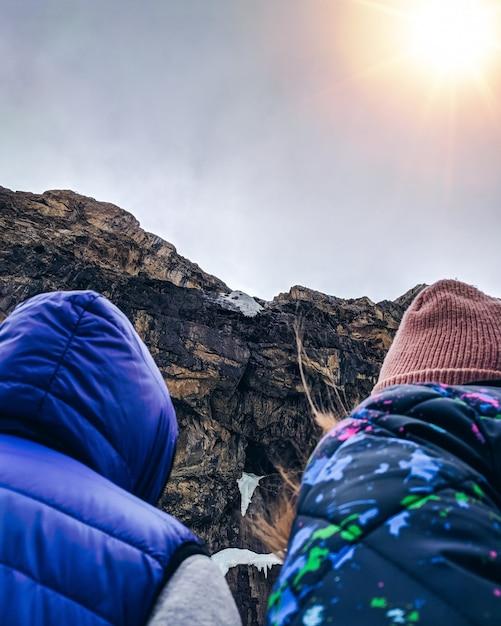 Two tourists enjoying sunset on top of a mountain. Premium Photo