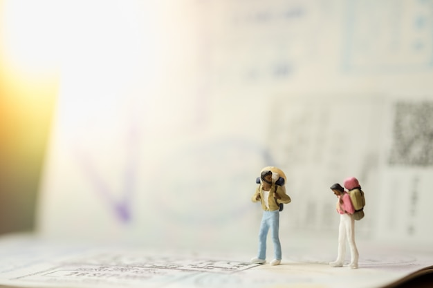 Two of traveler miniature mini figures with backpack standing and talking on passport with immigration stamps Premium Photo