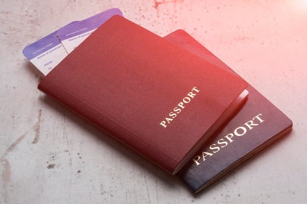 Two travelers passports red and blue with boarding passes for the plane. Premium Photo