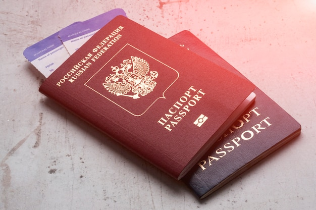 Two travelers passports russian and belarus with boarding passes for the plane. t Premium Photo