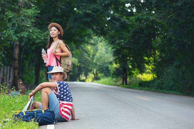 Двое путешественников сидят на проселочной улице Бесплатные Фотографии