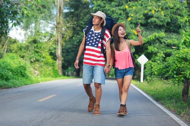 Двое путешественников, идущих по проселочной улице Бесплатные Фотографии
