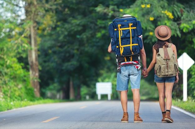 田舎道を歩く2人の旅行者 無料写真