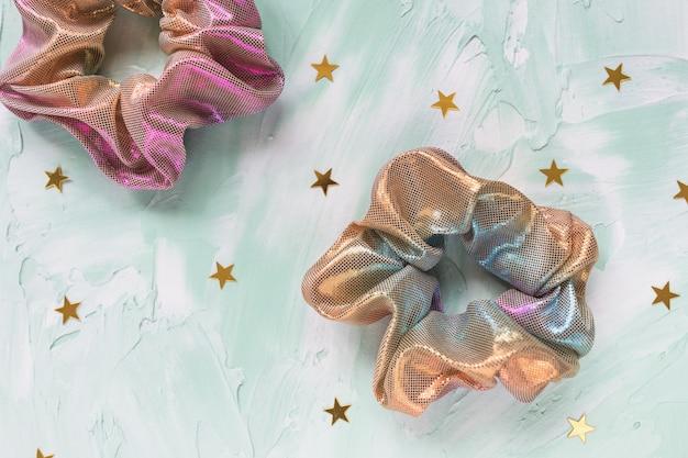 Две модные голографические резинки для волос и конфетти с золотыми звездами на зеленом столе Premium Фотографии