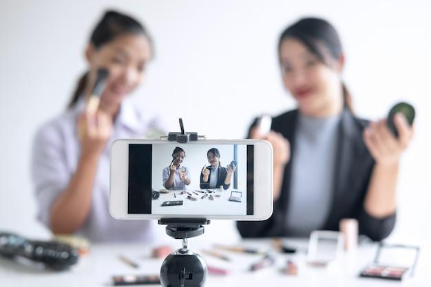 ソーシャルメディアでオンラインビジネスを行うtwo two woman bloggerは、現在のチュートリアル美容化粧品を公開しており、オンライン教育を記録しながらソーシャルネットワークにライブストリーミングビデオを放送しています Premium写真