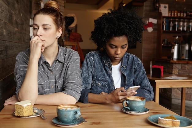 コーヒーショップで昼食時に口論した後2つの不幸なレズビアンがお互いに話していない 無料写真