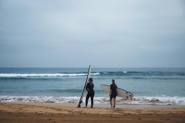 Due ragazze surfiste irriconoscibili con le loro longboard rimangono sulla riva dell'oceano e guardano le onde al mattino presto, indossando mute intere e pronte a fare surf Foto Gratuite