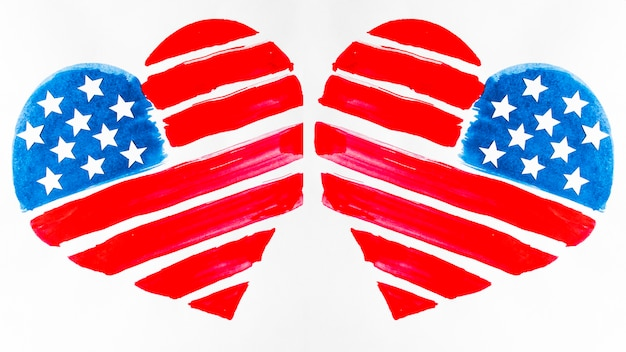 Two usa flag painted heart shapes on white background Free Photo