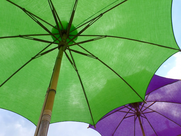 b450ec47e Two vibrant colored parasols, one green and one purple against sunny blue  sky, thailand Premium Photo