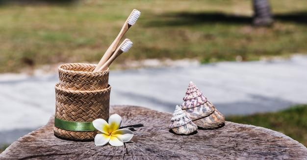 Две белые и желтые экологически чистые бамбуковые деревянные зубные щетки в держателе на деревянном Premium Фотографии