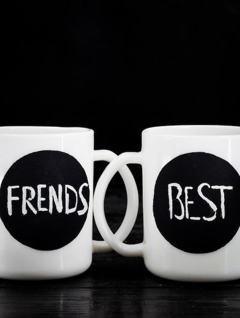 黒い木、休日の概念の上に碑文立って2つの白いカップ 無料写真