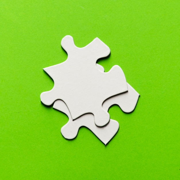 Two white jigsaw puzzle piece on bright green backdrop Free Photo