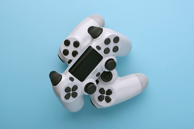 Two white joystick gamepad, game console on blue colourful trendy modern fashion pin-up background Premium Photo
