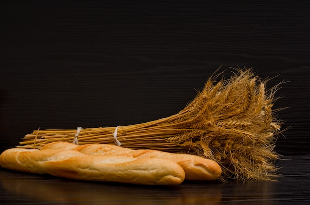 Two white loaf and a sheaf on a black background, with space for text Premium Photo