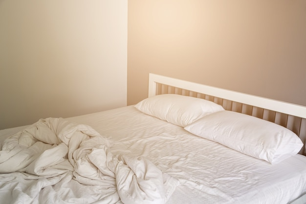 Two White Pillow On Bed With Wrinkle Messy Blanket In Bedroom