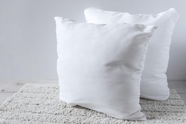 ふわふわの敷物の上に2つの白い枕。 Premium写真