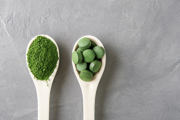 Two white spoon with chlorella or spirulina on a grey concrete background. top view. Premium Photo