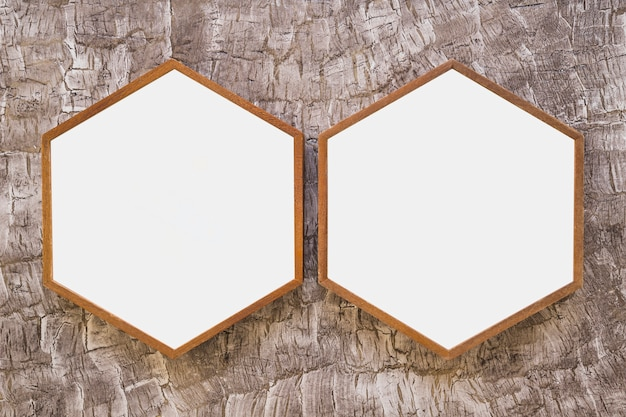 Two white wooden hexagon frame on wallpaper