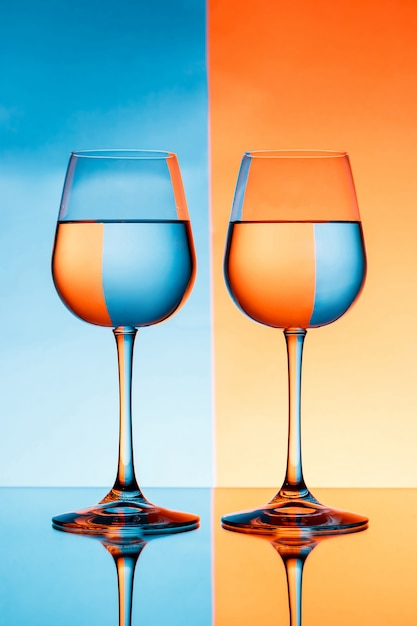 Due bicchieri di vino con acqua sulla parete blu e arancione Foto Gratuite