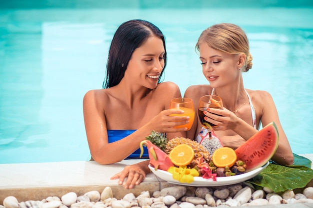 Two woman relaxing on luxury tropical vacation near with big plates with different tasty sweet exotic fruits in the pool Premium Photo
