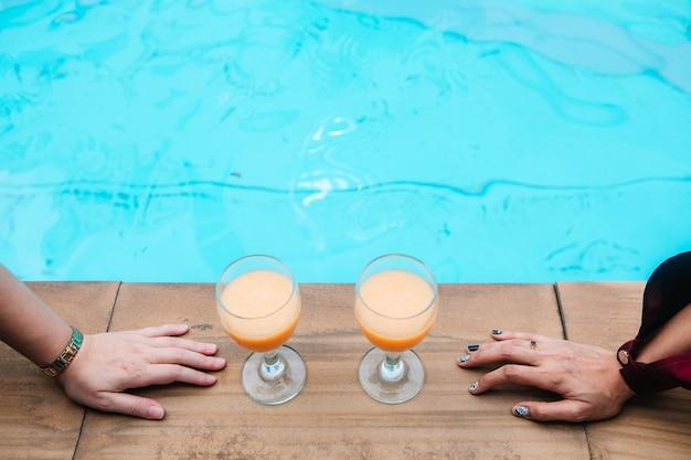 Two women are drinking orange juice by the sea. Premium Photo