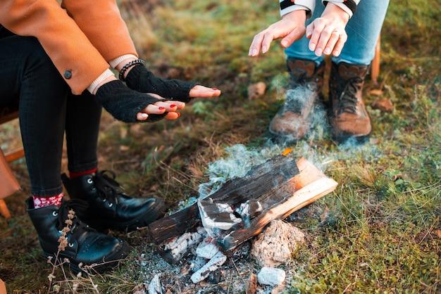 2人の女性が野原で燃えている木の近くでウォーミングアップしています Premium写真