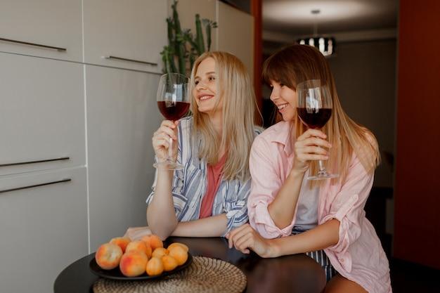 キッチンでワインを楽しむ2人の女性の親友。居心地の良い家庭的な雰囲気。新鮮な果物を盛り付けます。 無料写真