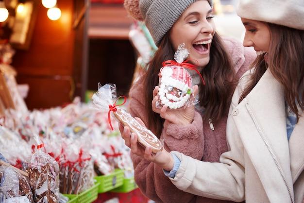 クリスマスマーケットで生姜パンを買う2人の女性 無料写真