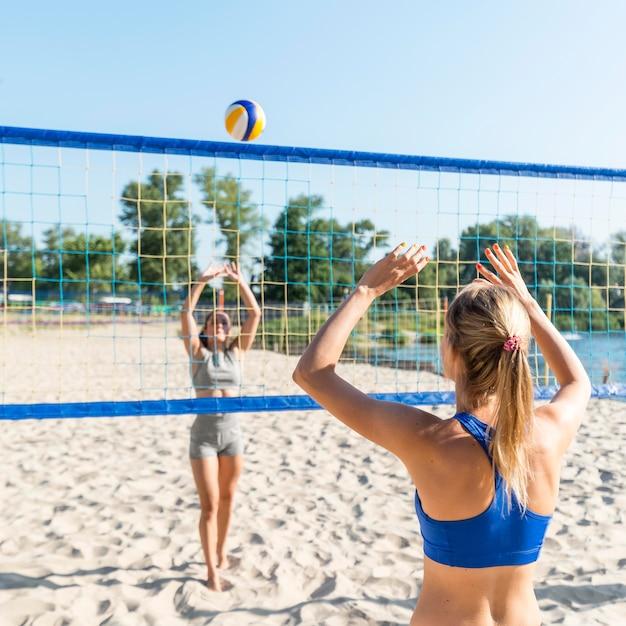 Due donne sulla spiaggia che giocano a pallavolo Foto Gratuite