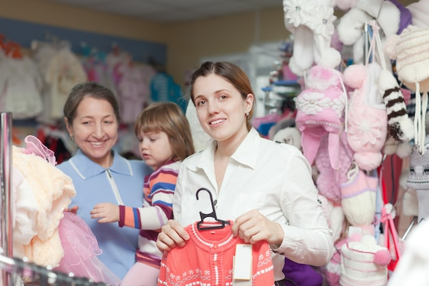 Two women and child  at clothes store Free Photo