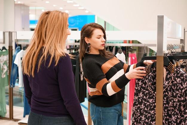 Due donne scelgono i vestiti in un negozio Foto Gratuite