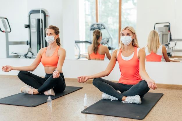 Две женщины занимаются йогой в тренажерном зале с медицинскими масками на Бесплатные Фотографии