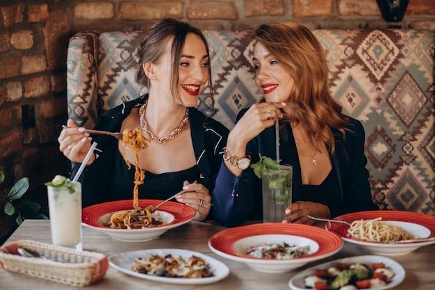 Две женщины едят пасту в итальянском ресторане Бесплатные Фотографии