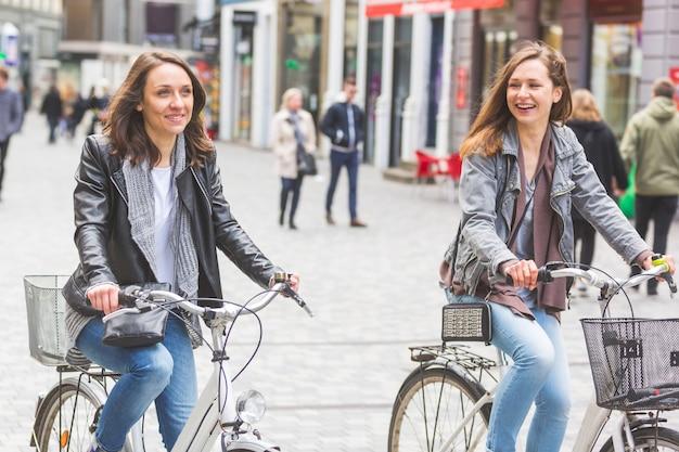 Two women going by bike in copenhagen. Premium Photo