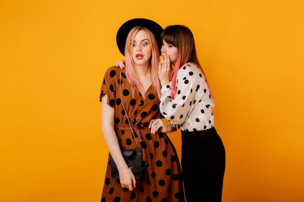 Две женщины сплетничают над желтой стеной в стильном винтажном наряде Бесплатные Фотографии