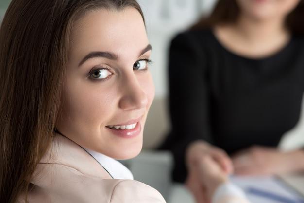 Рукопожатие двух женщин в офисе. деловые женщины, пожимая руки. леди оглядывается через плечо. концепция партнерства, бизнеса и сотрудничества. партнеры заключили сделку. официальный приветственный жест Premium Фотографии